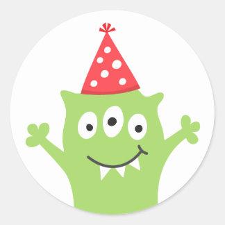 Monstruo divertido con el gorra del fiesta pegatina redonda