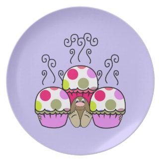 Monstruo lindo con las magdalenas rosadas y púrpur platos