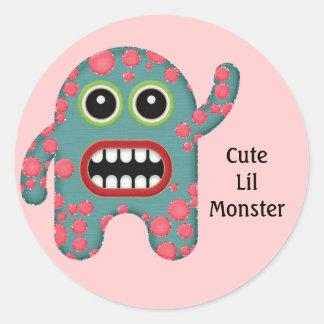Monstruo sonriente dentudo azul y rosado lindo etiqueta redonda