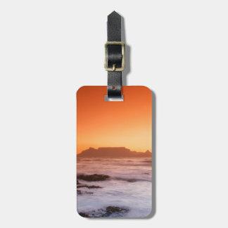 Montaña de la tabla en la puesta del sol, etiquetas maletas