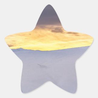 Montañas abstractas con nieve en la puesta del sol pegatina en forma de estrella