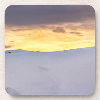 Montañas abstractas con nieve en la puesta del sol posavasos de bebidas