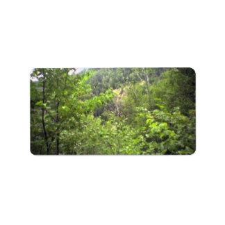 Montañas con las plantas y los árboles etiqueta de dirección