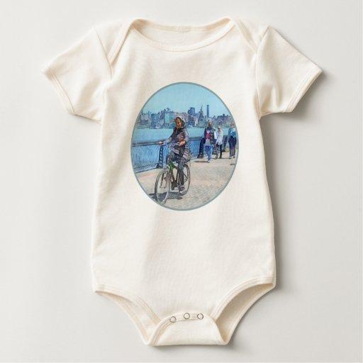 Montando en bicicleta a lo largo del embarcadero trajes de bebé