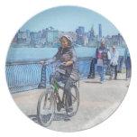 Montando en bicicleta a lo largo del embarcadero u platos para fiestas