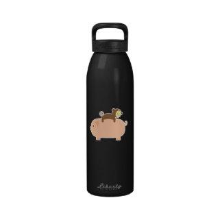 Montar a caballo del mono del bebé en un cerdo botallas de agua