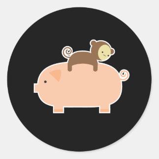 Montar a caballo del mono del bebé en un cerdo pegatina redonda