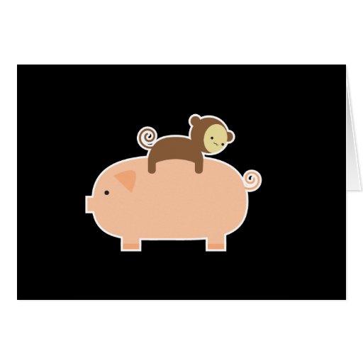 Montar a caballo del mono del bebé en un cerdo tarjeton