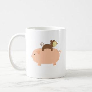 Montar a caballo del mono del bebé en un cerdo taza de café