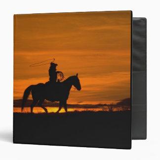 """Montar a caballo del vaquero en la puesta del sol  carpeta 1 1/2"""""""