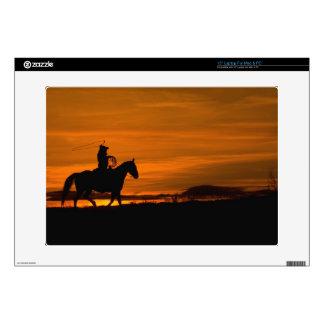Montar a caballo del vaquero en la puesta del sol  portátil 38,1cm skin