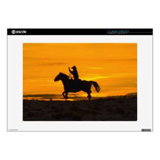 Montar a caballo del vaquero en la puesta del sol  skins para 38,1cm portátiles