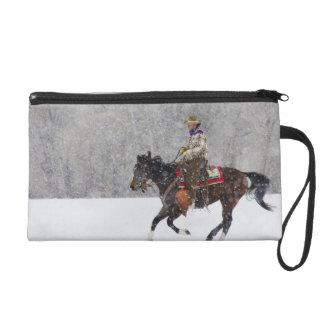 Montar a caballo del vaquero en nevadas