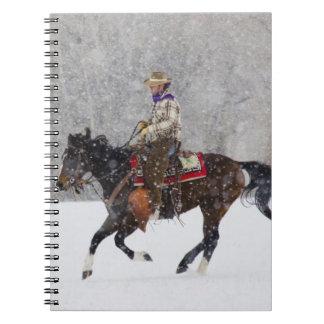 Montar a caballo del vaquero en nevadas libros de apuntes