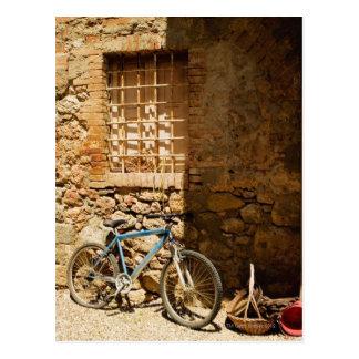 Monte en bicicleta delante de una pared, postal