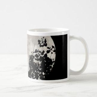 Moon behind dark leaves coffee mug