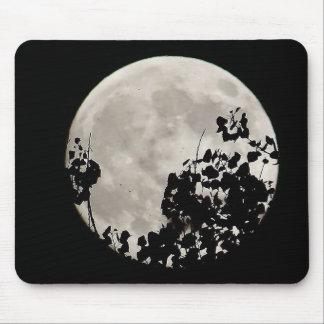 Moon behind dark leaves mouse pad