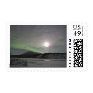 Moon rises over curtain of green aurora borealis postage