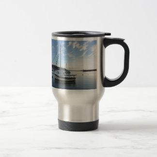 Moored sailing cutter at dawn. coffee mugs