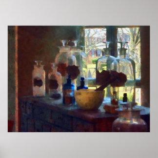 Mortero maja y botellas por la ventana impresiones