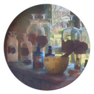Mortero, maja y botellas por la ventana platos