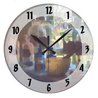 Mortero, maja y botellas por la ventana reloj redondo grande