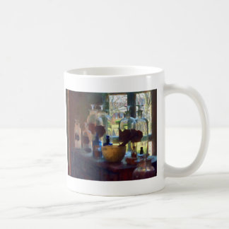 Mortero, maja y botellas por la ventana taza de café