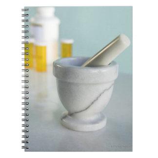 Mortero y maja, botellas de píldora en fondo cuaderno