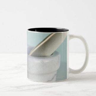Mortero y maja, botellas de píldora en fondo taza de café de dos colores