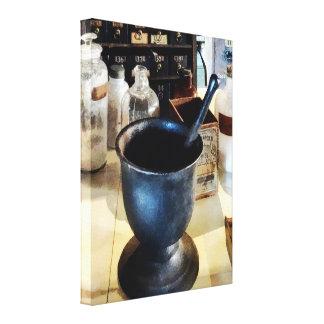 Mortero y maja cerca de las botellas de la impresión en lienzo estirada