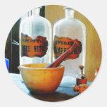 Mortero y maja con las botellas etiquetas redondas