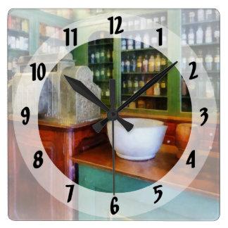 Mortero y maja en farmacia reloj cuadrado