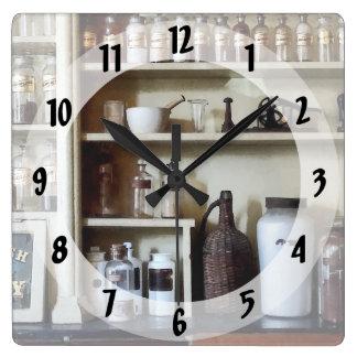 Mortero y maja y botellas en estantes reloj cuadrado