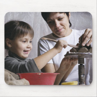 mother and daughter forming sculpture out of mousepads