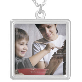 mother and daughter forming sculpture out of silver plated necklace