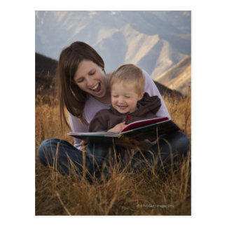 Mother and son reading outdoors postcard