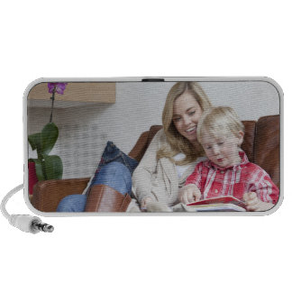 Mother and son sitting on sofa together portable speaker
