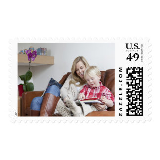 Mother and son sitting on sofa together postage stamp