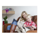Mother and son sitting on sofa together postcard