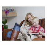 Mother and son sitting on sofa together poster