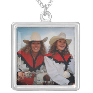 Mother and teenage daughter (14-16) at rodeo, silver plated necklace