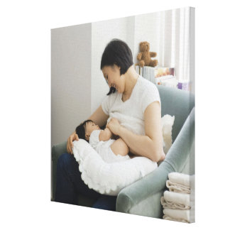 Mother breast feeding baby girl stretched canvas print
