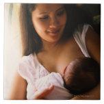 Mother breast feeding newborn ceramic tile