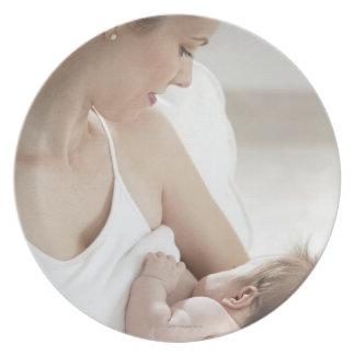 Mother breastfeeding baby 2 dinner plate