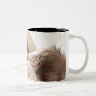 Mother breastfeeding baby 2 mugs