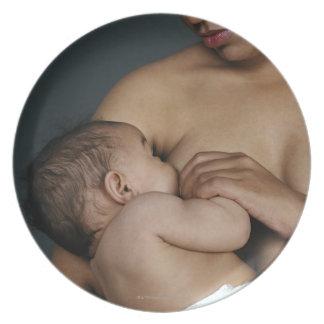 Mother breastfeeding baby boy (6-11 months) plate