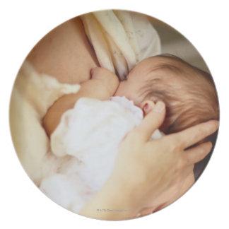 Mother breastfeeding baby girl (1-3 months) dinner plate
