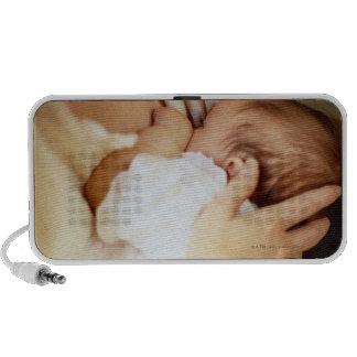 Mother breastfeeding baby girl (1-3 months) travelling speaker