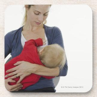 Mother breastfeeding her baby. drink coasters