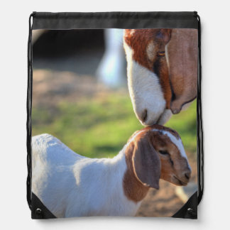 Mother goat kissing her baby on head. drawstring backpack